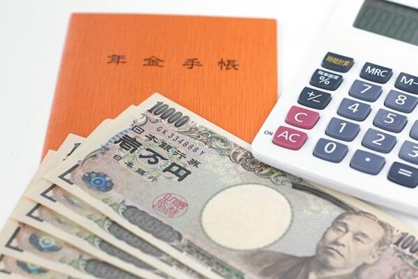 年金手帳と1万円札と電卓