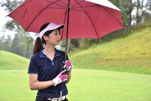 ゴルフ場で傘を差すゴルファー