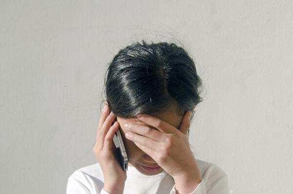 泣きながら電話する女性