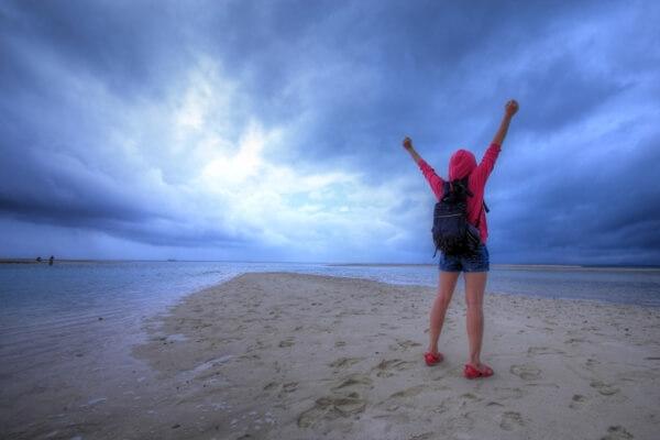 砂浜でバンザイする女性