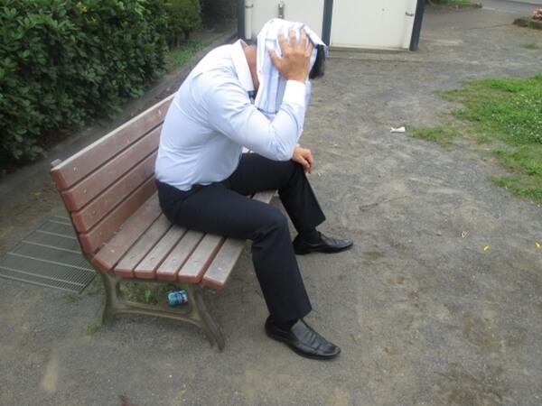熱中症でベンチで休む男性