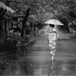 雨の中を歩く着物の女性