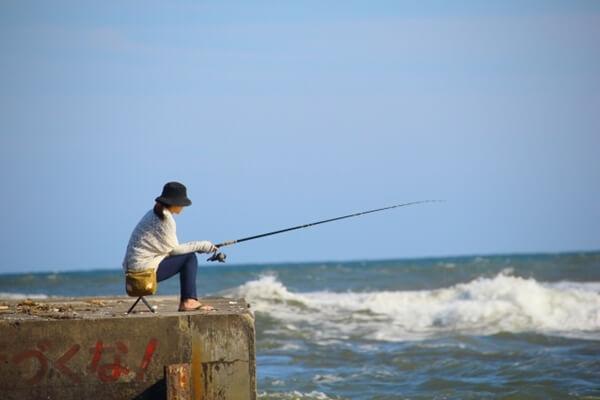 堤防で釣りをする女性